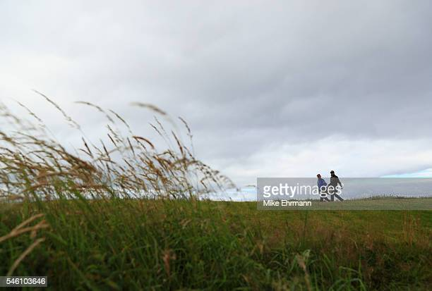 Jon Curran of the United States walks with his caddie during previews ahead of the 145th Open Championship at Royal Troon on July 11 2016 in Troon...