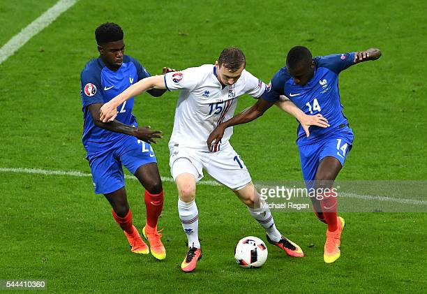 Jon Dadi Bodvarsson of Iceland competes against Samuel Umtiti and Blaise Matuidi of France during the UEFA EURO 2016 quarter final match between...