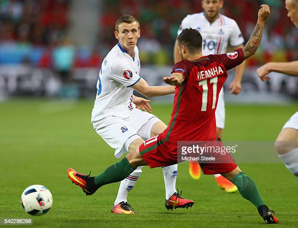 Jon Dadi Bodvarsson of Iceland slips the ball past Vieirinha of Portugal during the UEFA EURO 2016 Group F match between Portugal and Iceland at...