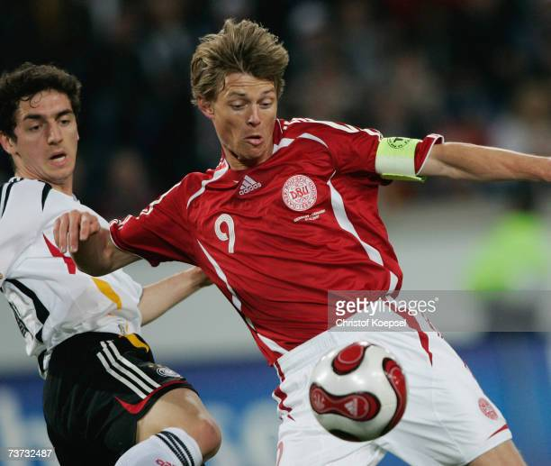 Jon Dahl Tomasson of Denmark has a shot as Roberto Hilbert of Germany tries to block him during the international friendly match between Germany and...