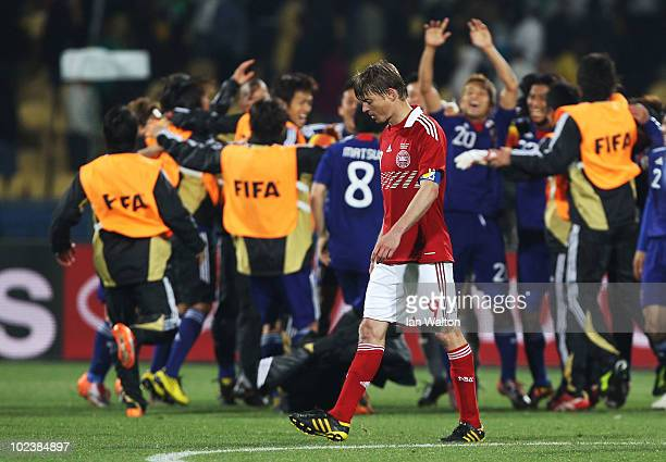 Jon Dahl Tomasson of Denmark leaves the pitch dejected as Japan players celebrate victory during the 2010 FIFA World Cup South Africa Group E match...