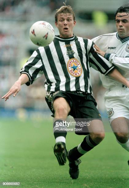 Jon Dahl Tomasson of Newcastle United holds off Stephen Carr of Tottenham Hotspur during an FA Carling Premiership match at St James' Park on October...