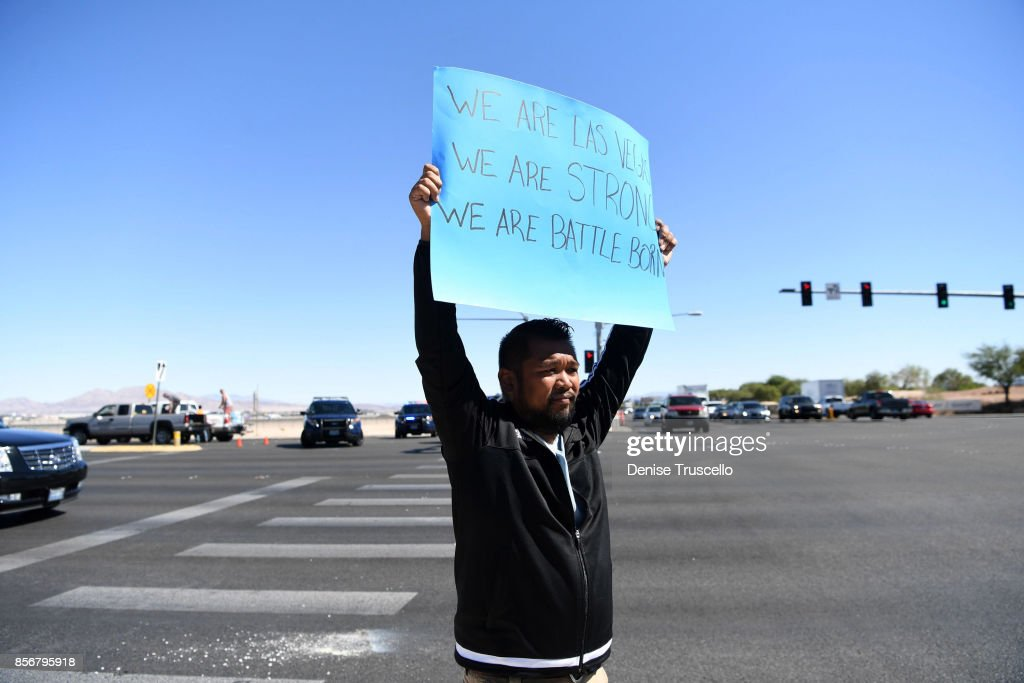 Jon Dimaya of Las Vegas, a rapid response team nurse at Sunrise Hospital, holds a sign on Las Vegas Boulevard, October 2, 2017 in Las Vegas, Nevada. Stephen Paddock, 64, of Mesquite, Nevada allegedly opened fire on festival attendees from his room in the Mandalay Bay Hotel and Casino leaving at least 58 dead and over 500 injured before reportedly killing himself.