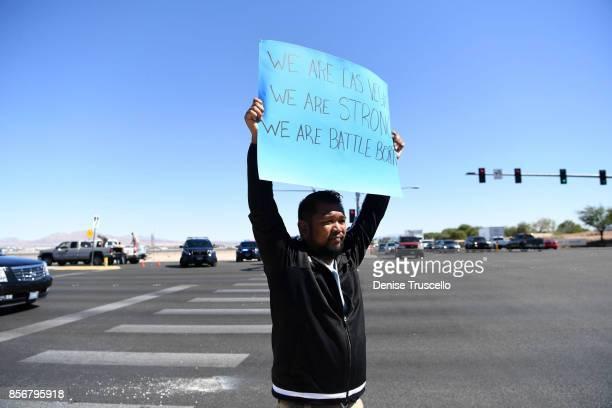 Jon Dimaya of Las Vegas, a rapid response team nurse at Sunrise Hospital, holds a sign on Las Vegas Boulevard, October 2, 2017 in Las Vegas, Nevada....