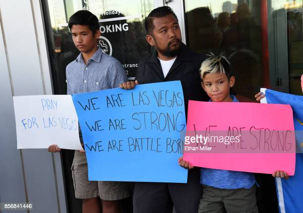 Jon Dimaya of Nevada a rapid response team nurse at Sunrise Hospital Medical Center and his sons Ethan Dimaya and Gryffin Dimaya hold signs during a...