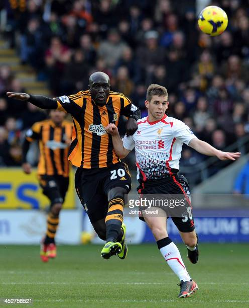 Jon Flanagan of Liverpool competes with Yannick Sagbo of Hull City during the Barclays Premier League match between Hull City and Liverpool at the KC...
