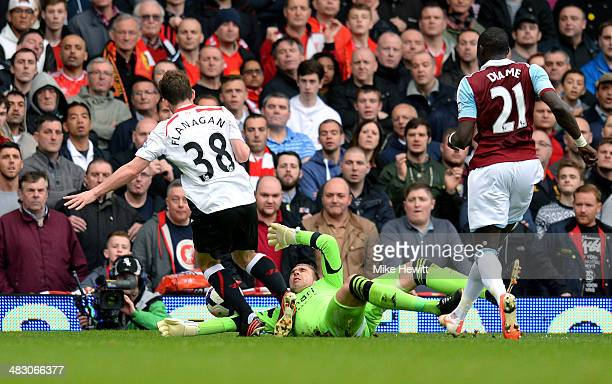 Jon Flanagan of Liverpool is brought down by goalkeeper Adrian of West Ham to earn a penalty during the Barclays Premier League match between West...