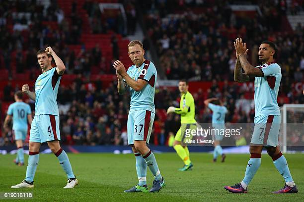 Jon Flanagan Scott Arfield and Andre Gray of Burnley applaud supporters after their team's scoreless draw in the Premier League match between...