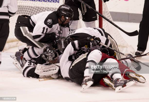 Jon Gillies, Niko Rufo, and Kevin Hart all of the Providence College Friars pile in the crease against the Miami University RedHawks during NCAA...
