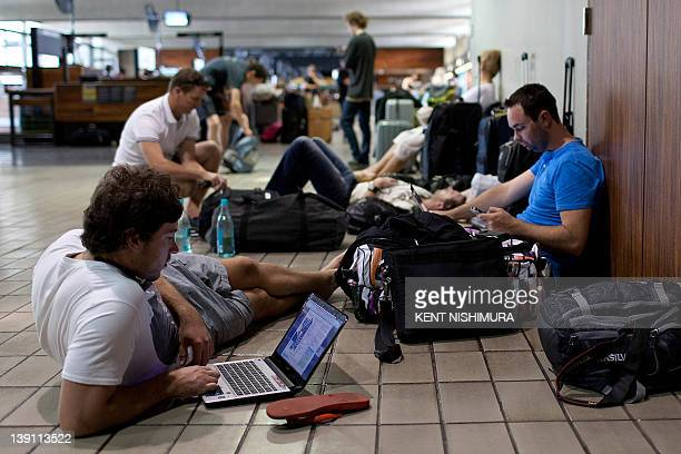 Jon Gray of Brisbane surfs the Internet on his laptop for alternative flights to Australia near the Air Australia ticket counter at Honolulu...