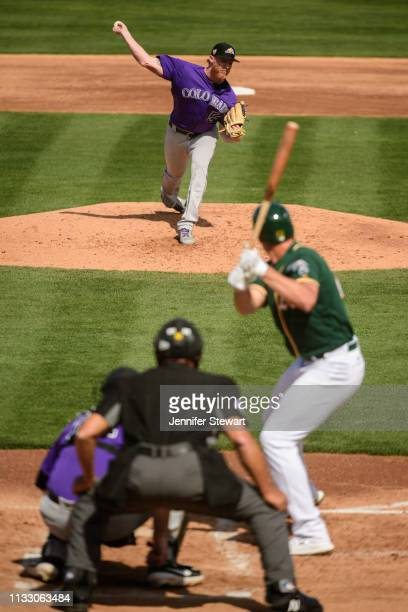 Jon Gray of the Colorado Rockies delivers a pitch to Matt Olson of the Oakland Athletics during the spring training game at HoHoKam Stadium on March...