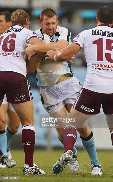 Jon Green of the Sharks is tackled during the NRL trial match between the Cronulla Sharks and the Manly Warringah Sea Eagles at Toyota Stadium on...
