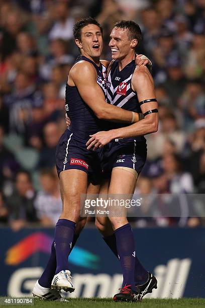 Jon Griffin of the Dockers is congratulated by Matthew Pavlich after kicking a goal during the round 16 AFL match between the Fremantle Dockers and...