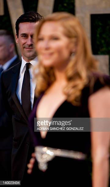 Jon Hamm watches Jennifer Westfeldt have her photo taken on the carpet as they arrive at the Vanity Fair Oscar Party for the 84th Annual Academy...