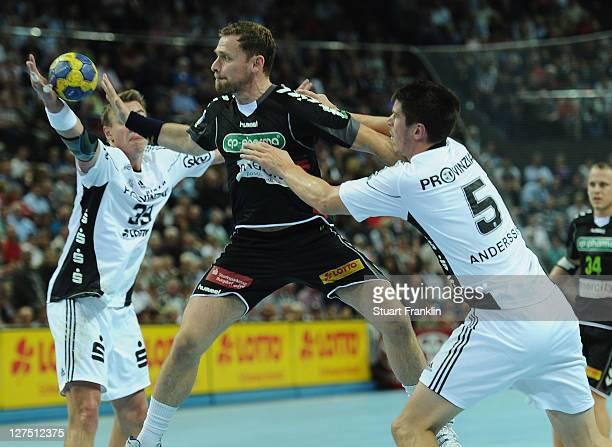 Jon Hannes Jonsson of Hannover is challenged by Filip Jicha and Kim Andersson of Kiel during the Toyota handball Bundesliga match between THW Kiel...
