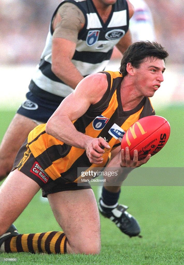 Jon Hassall of Hawthorn hand balls under pressure, in the match between Geelong and Hawthorn, during round six of the AFL season, played at Kardinia Park, Geelong, Australia. Mandatory Credit: Mark Dadswell/ALLSPORT