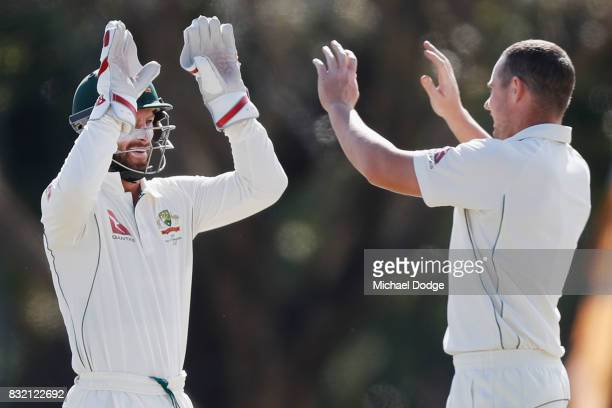 Jon Holland celebrates with Matthew Wade after dismissing Hilton Cartwright walks off after taking early wickets during day three of the Australian...