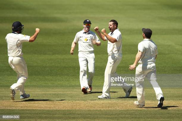Jon Holland of the Bushrangers celebrates with team mates after claiming the wicket of Jake Weatherald of the Redbacks during the Sheffield Shield...
