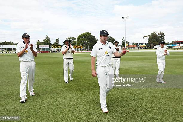 Jon Holland of the VIC Bushrangers is congratulated by teammates as Victorian players come from the field after South Australia was all bowled out...