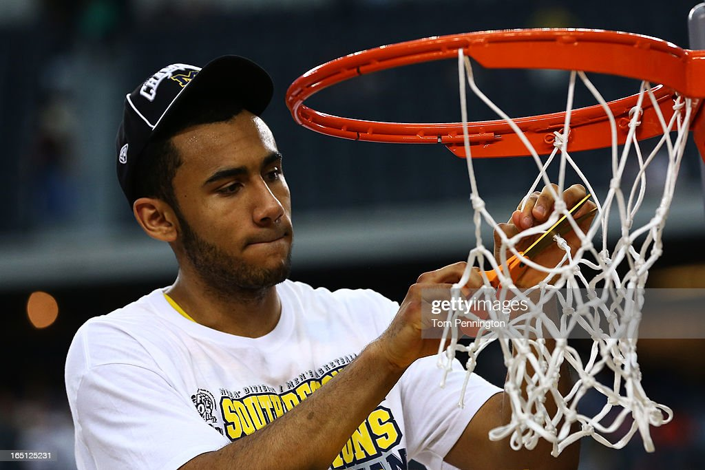 Jon Horford #15 of the Michigan Wolverines celebrates their 79 to 59 win over the Florida Gators by cutting down a piece of the net during the South Regional Round Final of the 2013 NCAA Men's Basketball Tournament at Dallas Cowboys Stadium on March 31, 2013 in Arlington, Texas.