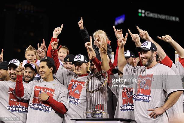 Jon Jay, Allen Craig and Lance Berkman of the St. Louis Cardinals celebrate with the World Series trophy after defeating the Texas Rangers 6-2 to win...