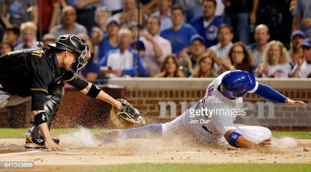 Jon Jay of the Chicago Cubs beats the tag of Chris Stewart of the Pittsburgh Pirates to score on an RBI single by Ian Happ during the first inning at...