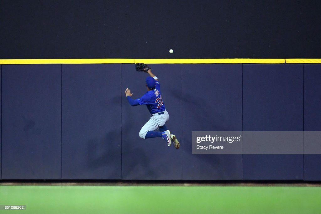 Jon Jay #30 of the Chicago Cubs is unable to catch a home run ball hit by Domingo Santana #16 of the Milwaukee Brewers during the fourth inning of a game at Miller Park on September 21, 2017 in Milwaukee, Wisconsin.