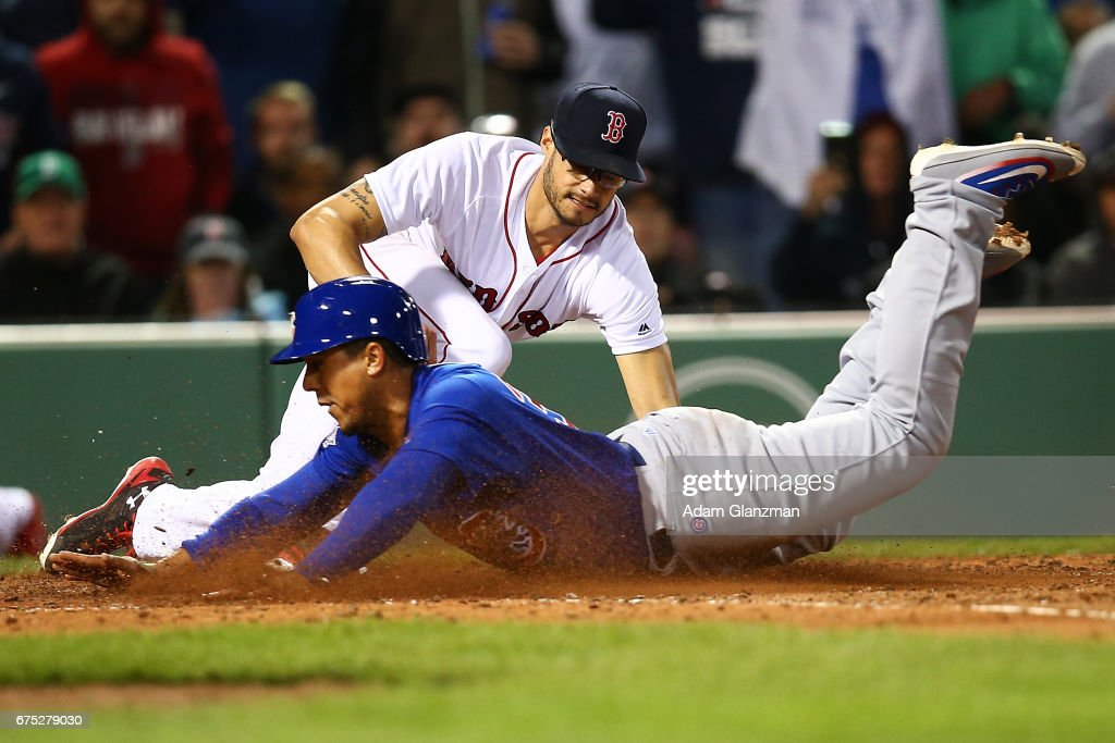 Jon Jay #30 of the Chicago Cubs slides safely into home plate under the tag of Joe Kelly #56 of the Boston Red Sox in the seventh inning of a game against at Fenway Park on April 30, 2017 in Boston, Massachusetts.