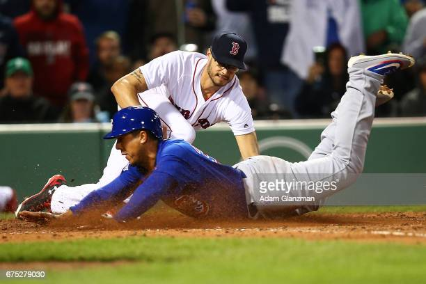 Jon Jay of the Chicago Cubs slides safely into home plate under the tag of Joe Kelly of the Boston Red Sox in the seventh inning of a game against at...