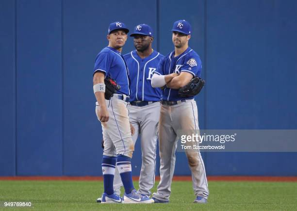 Jon Jay of the Kansas City Royals and Abraham Almonte and Whit Merrifield gather in the outfield during a pitching change in the seventh inning...