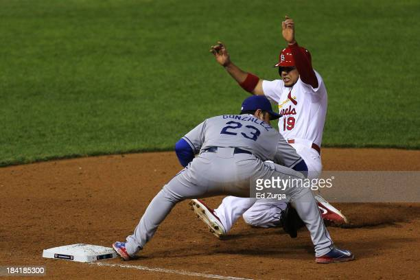 Jon Jay of the St. Louis Cardinals is out at first by Adrian Gonzalez of the Los Angeles Dodgers on a double play on a ball hit by David Freese in...