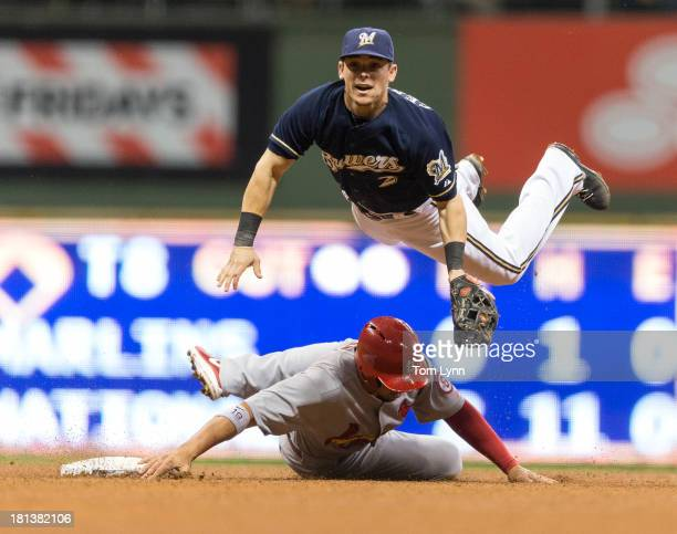 Jon Jay of the St Louis Cardinals slides into second and tries to break up a double play as Scooter Gennett of the Milwaukee Brewers leaps over the...