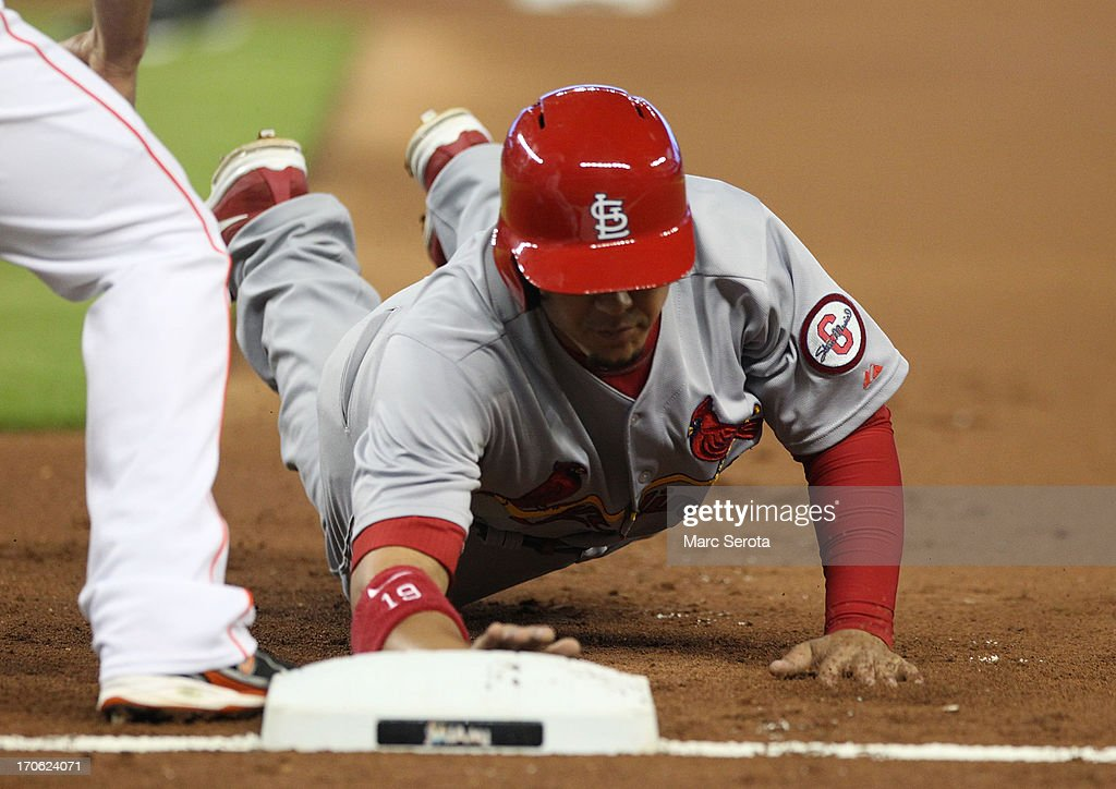 Jon Jay #19 of the St. Louis Cardinals slides safely into first base against the Miami Marlins during the first inning at Marlins Park on June 15, 2013 in Miami, Florida.
