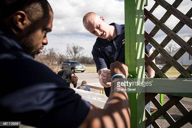 Jon Kreft and Isaiah Wilkerson of the Tulsa 66ers paint a pergola during the NBA DLeague community relations event at A New Leaf a nonprofit that...