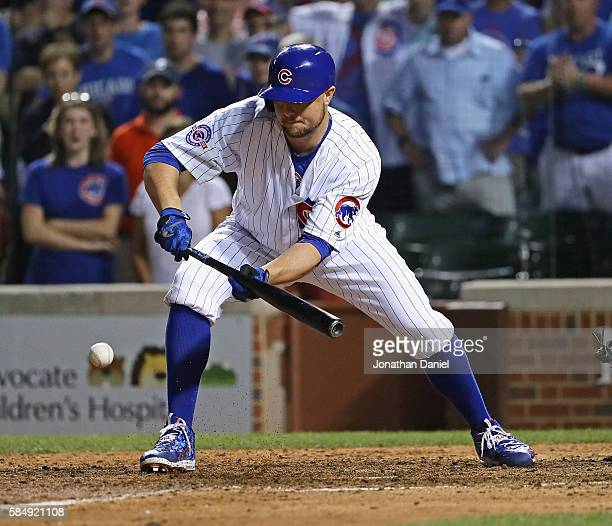 Jon Lester of the Chicago Cubs bunts in the winning run against the Seattle Mariners at Wrigley Field on July 31 2016 in Chicago Illinois The Cubs...