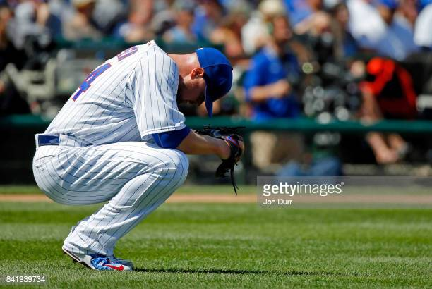 Jon Lester of the Chicago Cubs reacts after giving up a single to Matt Kemp of the Atlanta Braves to load the bases during the first inning at...