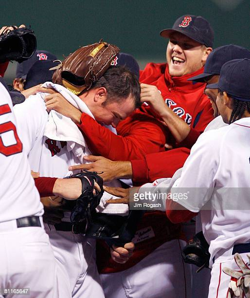 Jon Lester the Boston Red Sox is congratulated by Jonathan Papelbon and other teammates after throwing a no hitter against the Kansas City Royals at...