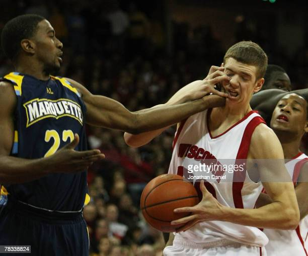 Jon Leuer of the Wisconsin Badgers gets his own hand and the hand Jerel McNeal of the Marquette Golden Eagles in his face at the Kohl Center December...