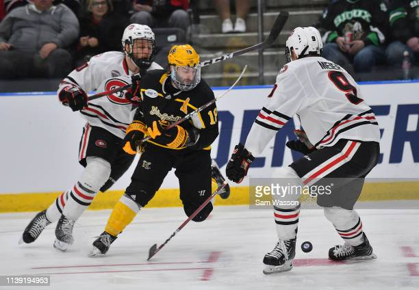 Jon Lizotte Spencer Meier of the St Cloud State Huskies and Blake Christensen of the American International Yellow Jackets battle for the puck during...