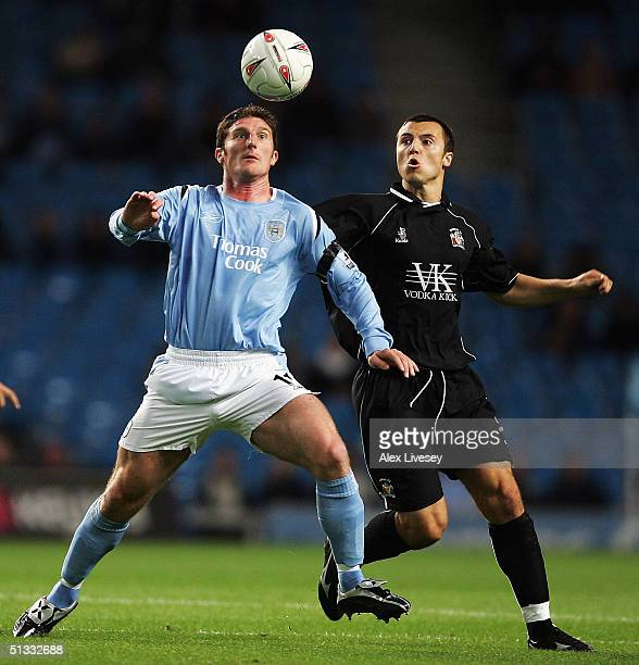 Jon Macken of Manchester City holds off a challenge from Antony Kay of Barnsley during the Carling Cup second round match between Manchester City and...
