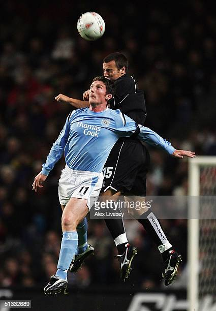 Jon Macken of Manchester City jumps with Antony Kay of Barnsley during the Carling Cup second round match between Manchester City and Barnsley at the...