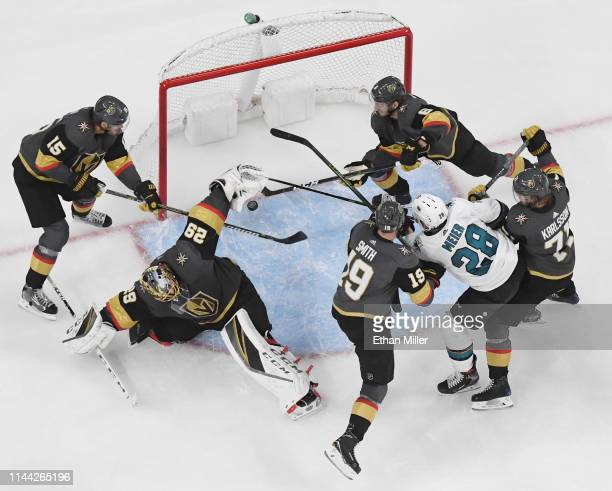 Jon Merrill and Colin Miller of the Vegas Golden Knights scramble behind MarcAndre Fleury of the Golden Knights to stop a shot by Timo Meier of the...