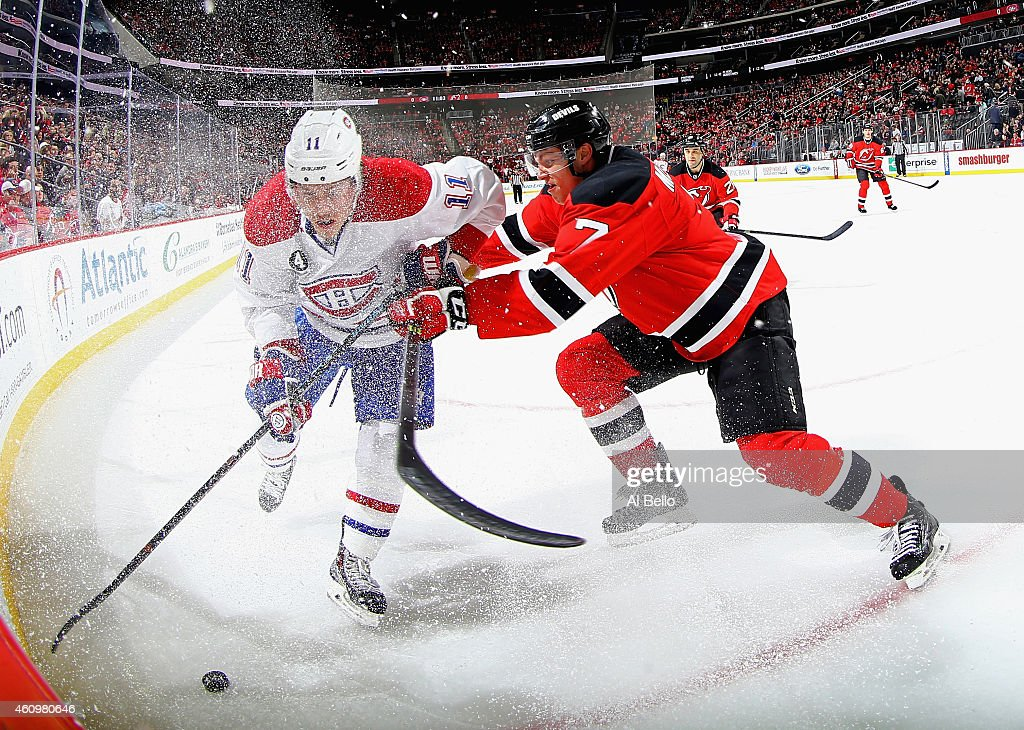 Jon Merrill #7 of the New Jersey Devils checks Brendan Gallagher #11 of the Montreal Canadiens during their game at the Prudential Center on January 2, 2015 in Newark, New Jersey.
