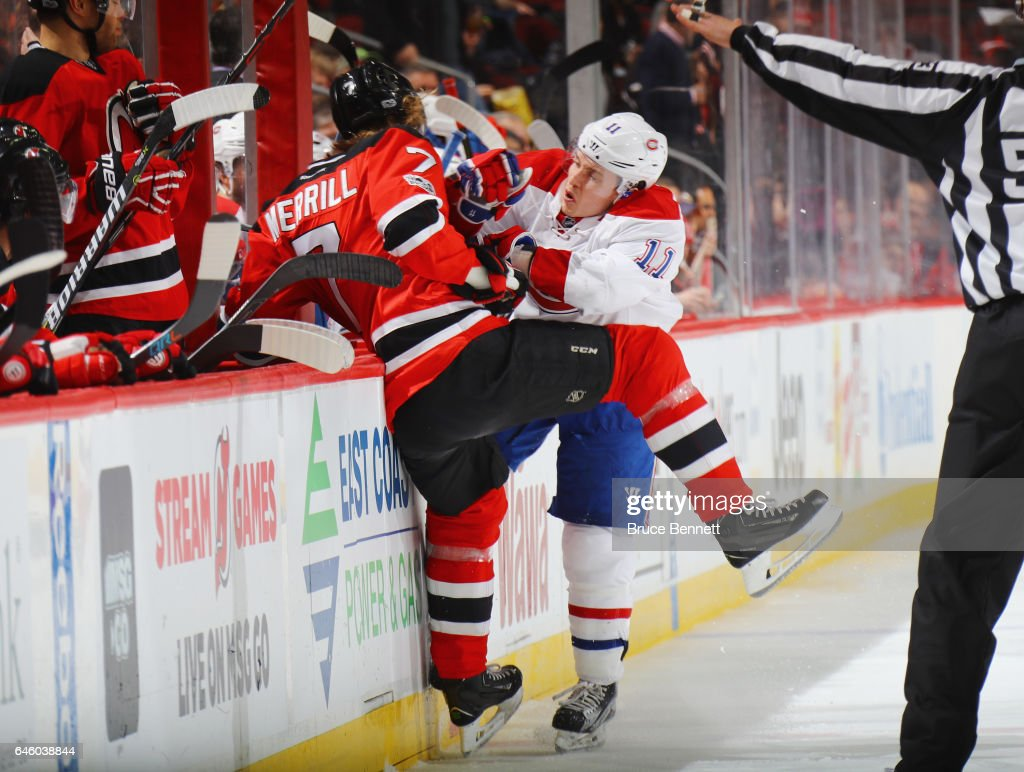 Jon Merrill #7 of the New Jersey Devils is checked into the boards by Brendan Gallagher #11 of the Montreal Canadiens during the first period at the Prudential Center on February 27, 2017 in Newark, New Jersey.