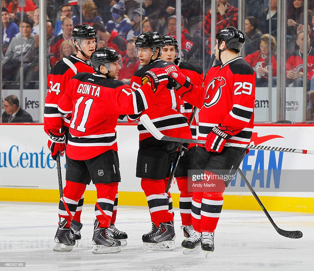 Jon Merrill #34 (L) of the New Jersey Devils is congratulated by teammates including Stephen Gionyta #11 and Ryane Clowe #29 after scoring the game-winning goal against the Toronto Maple Leafs during the game at the Prudential Center on March 23, 2014 in Newark, New Jersey. The Devils defeated the Leafs 3-2.