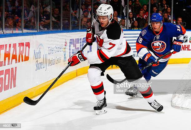 Jon Merrill of the New Jersey Devils is pursued by Ryan Strome of the New York Islanders at Nassau Veterans Memorial Coliseum on December 15 2014 in...