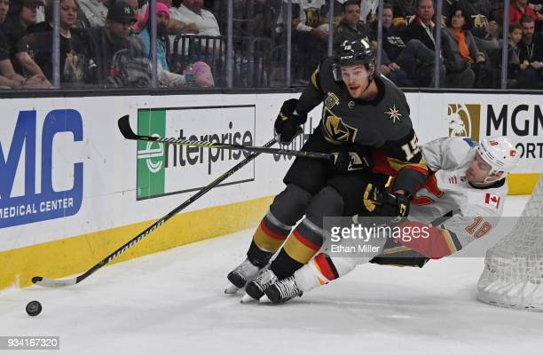 Jon Merrill of the Vegas Golden Knights and Matt Stajan of the Calgary Flames go after the puck in the first period of their game at TMobile Arena on...