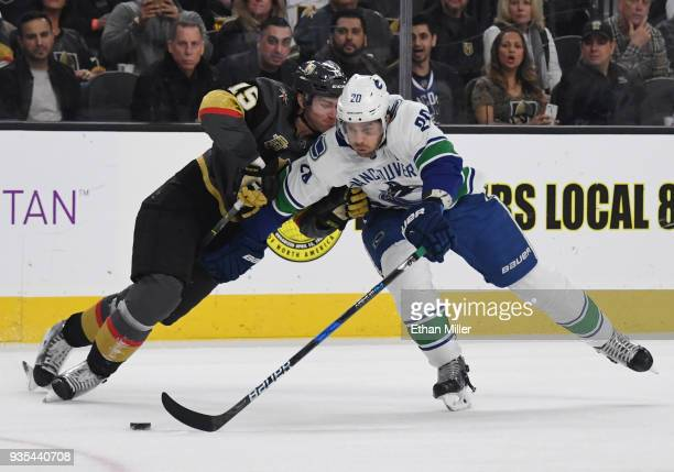 Jon Merrill of the Vegas Golden Knights hits Brandon Sutter of the Vancouver Canucks as he skates with the puck in the first period of their game at...