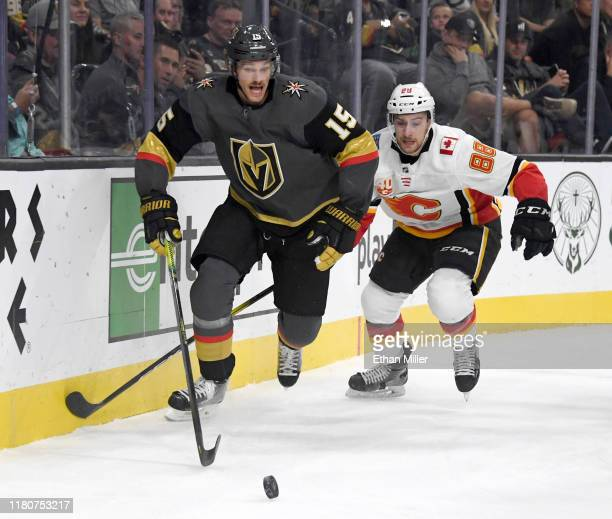 Jon Merrill of the Vegas Golden Knights tries to control the puck against Andrew Mangiapane of the Calgary Flames in the first period of their game...