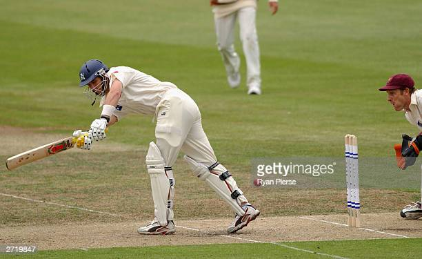 Jon Moss of Victoria plays a shot while Wade Secombe of Queensland watches on during the Pura Cup Cricket match between the Victorian Bushrangers and...